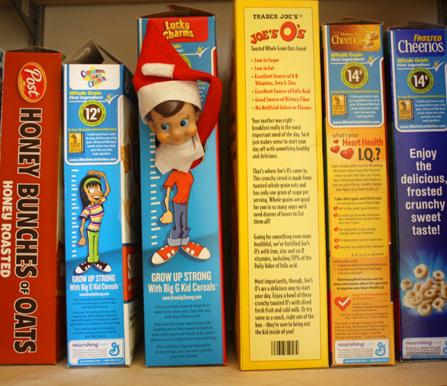 Elf on the Shelf measures his height on the cereal box