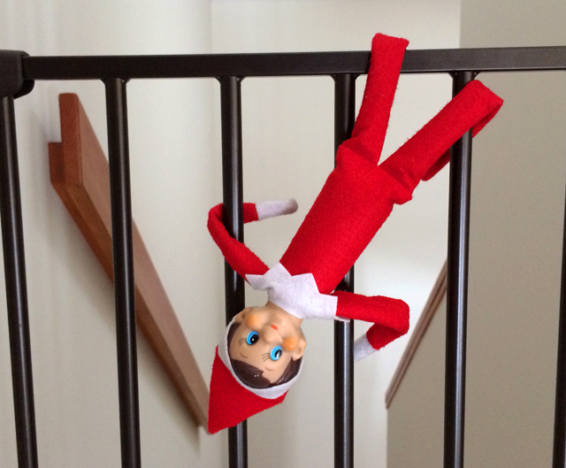 Elf on the Shelf swinging on the baby gate